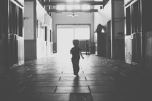 toddler boy running in a stable