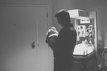 a father holding a newborn baby in a NICU
