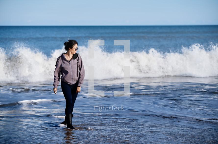 woman on a beach wearing rain boots