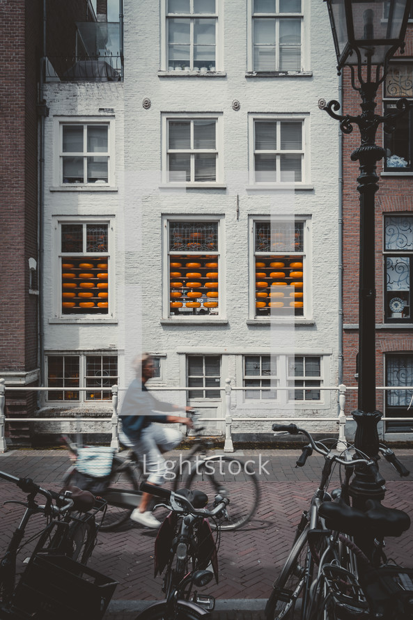 person riding a bicycle on a brick sidewalk