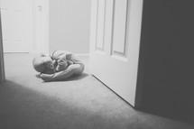A baby lays on the floor in a doorway.