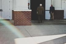 elderly man with a cane entering a church