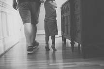 father and toddler son on a wood floor