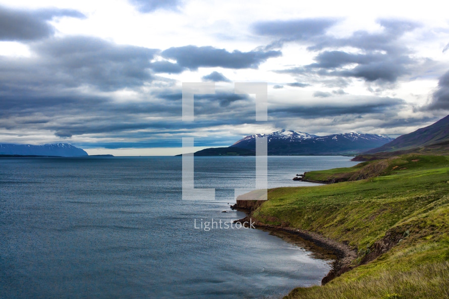 snow capped mountains and green shoreline