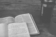 An open Bible and notebook next to a coffee mug and french press