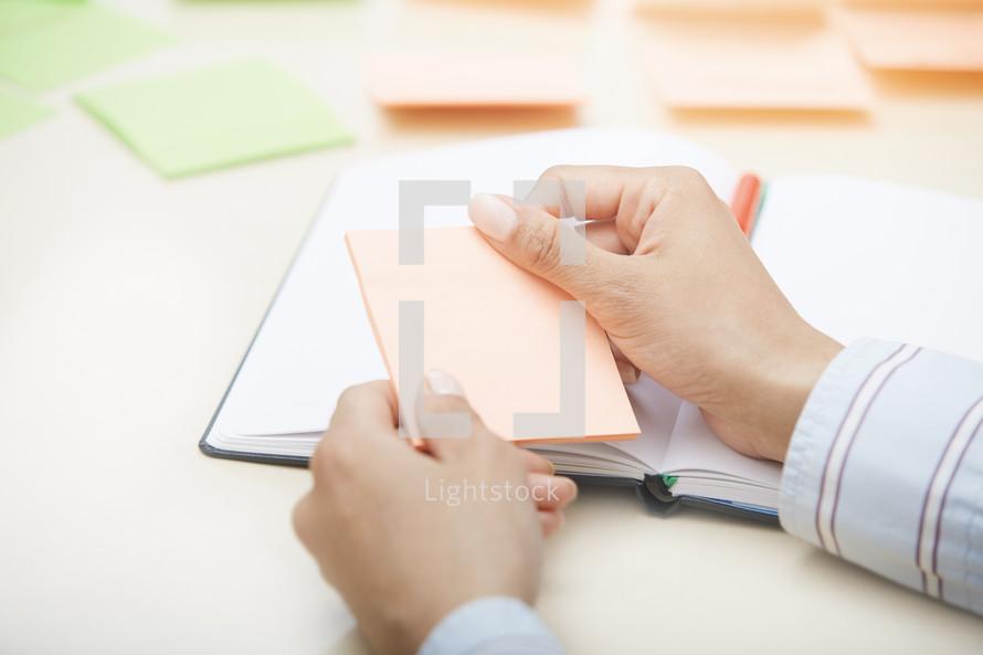 woman holding a blank sticky note