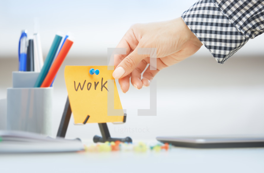 woman holding a sticky note with the word work