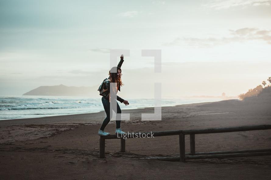 a woman balancing on a wood railing on a beach