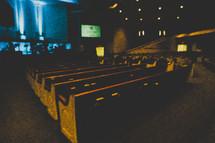 Empty pews in a dark church.