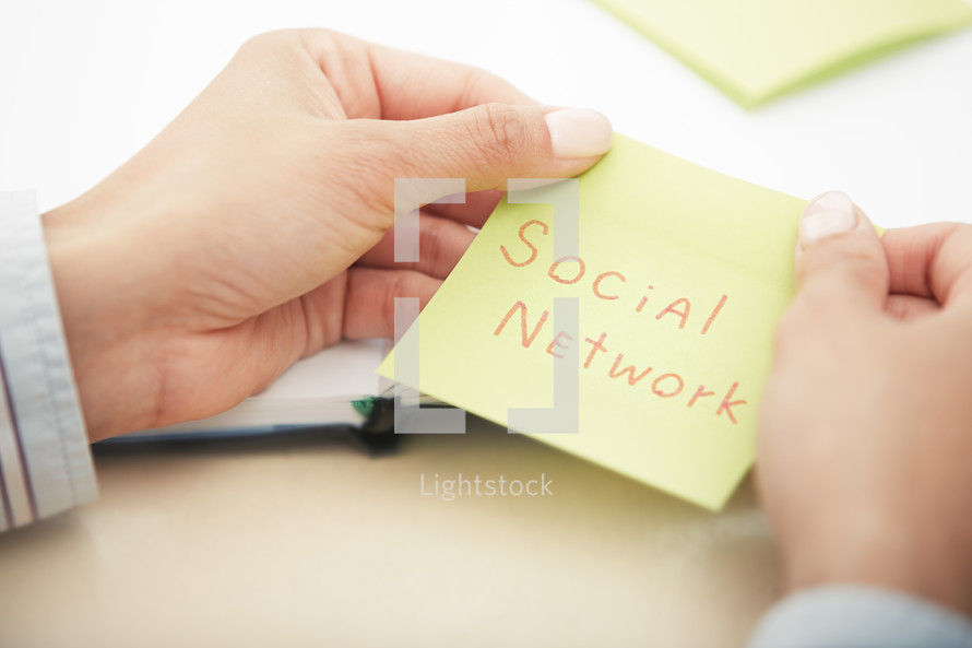 a woman reaching for a sticky note with the words social media