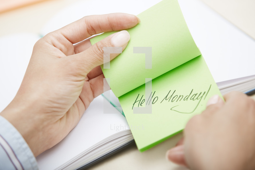 a woman reaching for a sticky note with the words hello Monday
