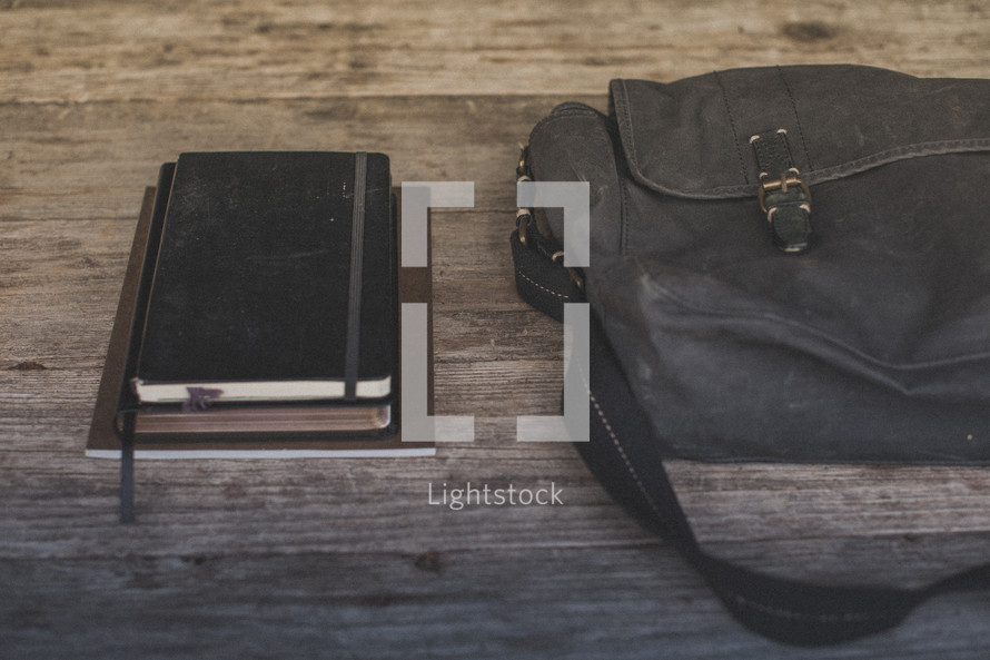 Notebooks and a Bible on a table next to a blue bag