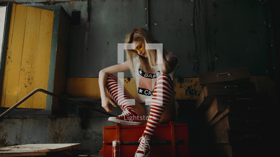 a woman in knee socks sitting on a red trunk