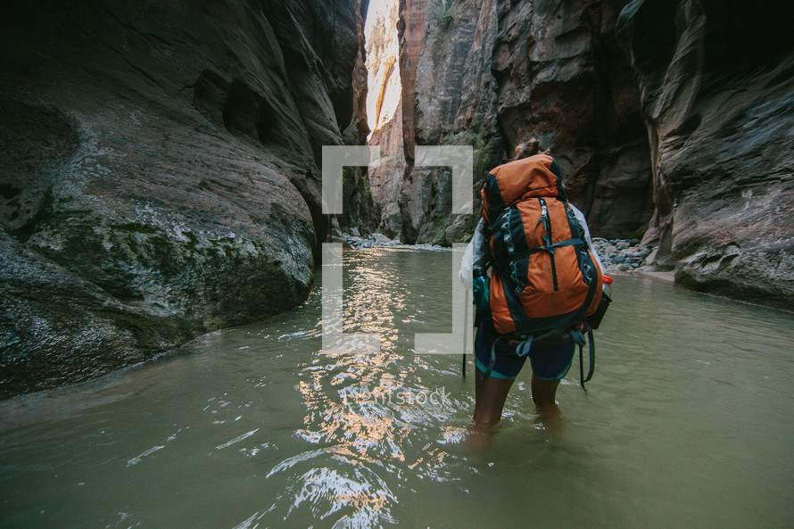 hiking through a river at the bottom of a canyon