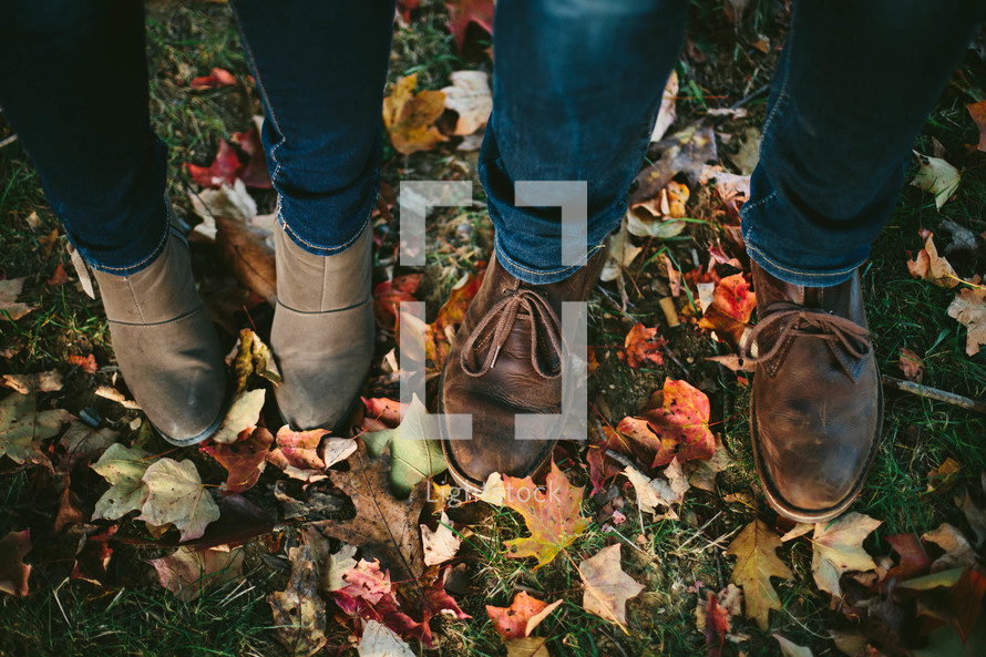 a couple in boots standing in fall leaves