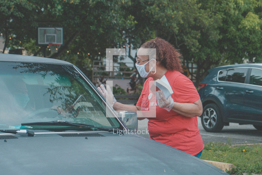 a woman wearing a face mask passing out Bibles