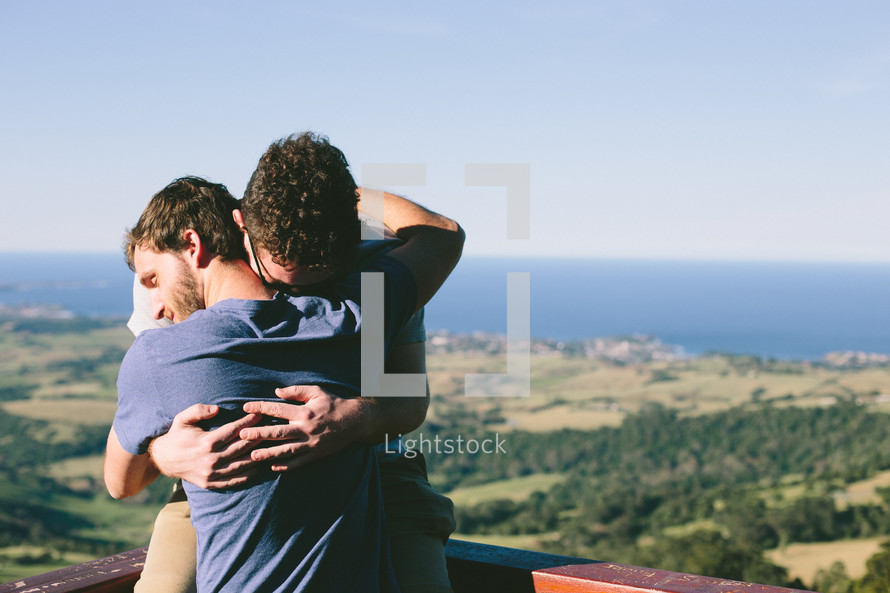 two men hugging outdoors