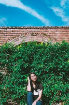 Young woman sitting in front of green ivy