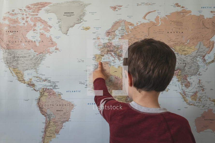 world map and child pointing to it