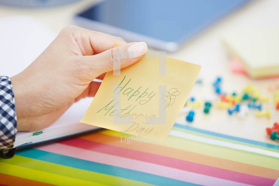 woman holding a sticky note with the words Happy Mother's day