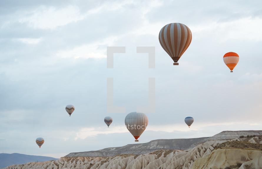 Hot air balloon flying over the rocky land. Cappadocia, Turkey