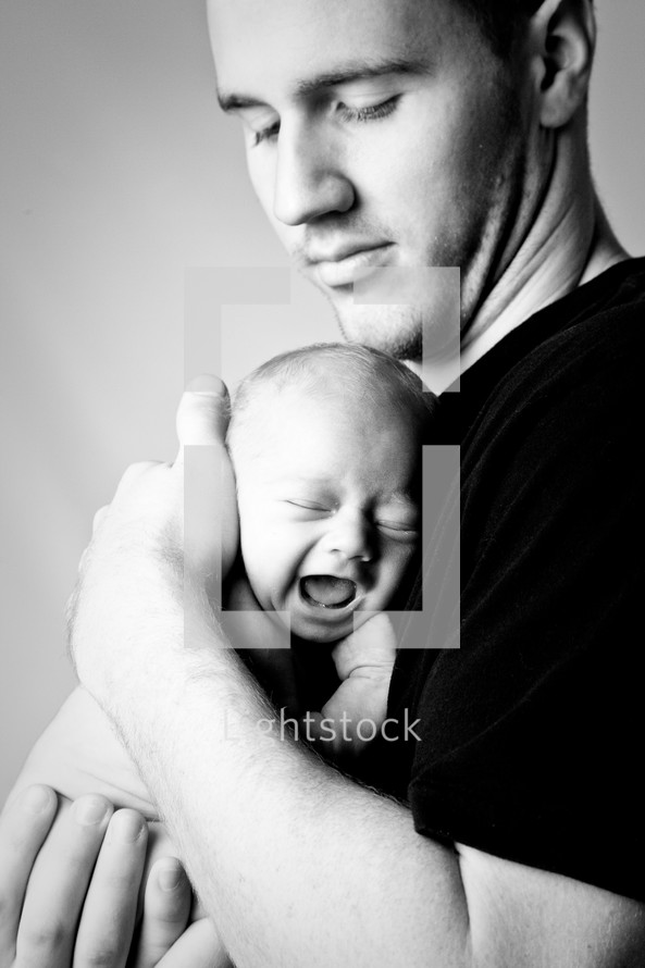 father holding a crying newborn