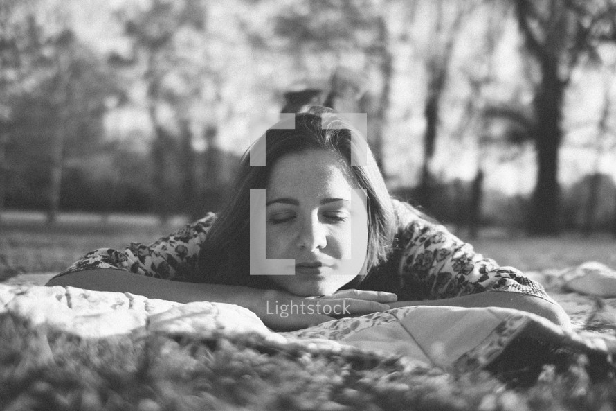 woman resting on a blanket in the grass