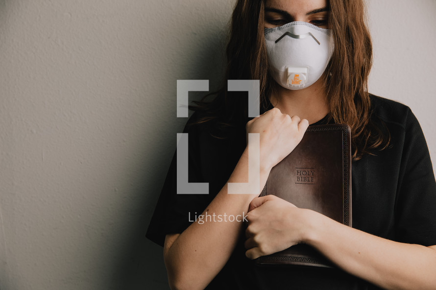 woman in a N95 mask holding a Bible