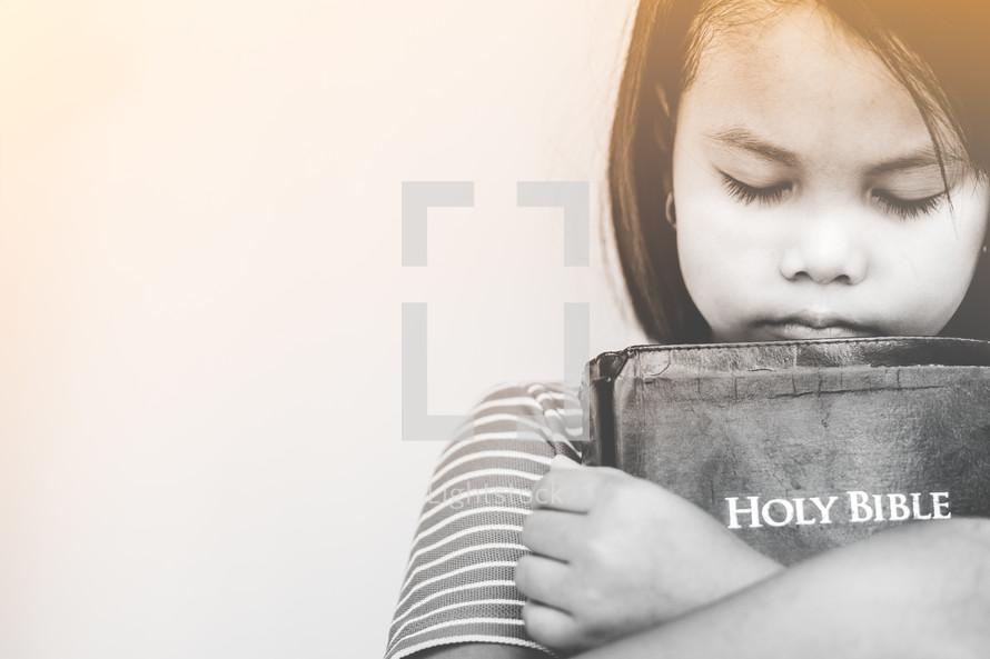 girl hugging a Bible