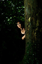 fearful woman peeking from behind a tree