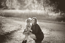 A little girl kissing her mother on the cheek.