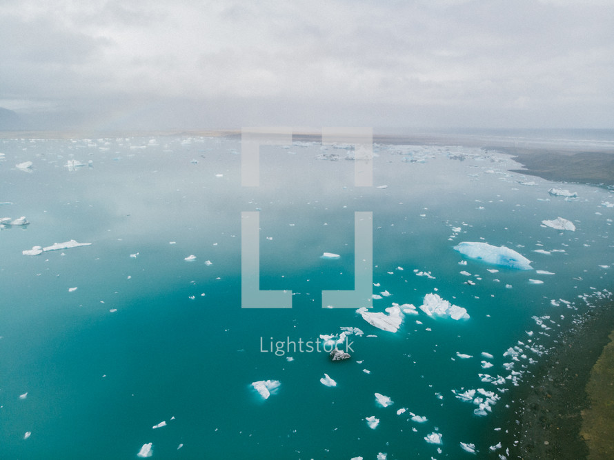aerial view over chunks of ice floating in the ocean