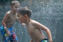 Two young boys playing in the sprinkler and getting sprayed with water