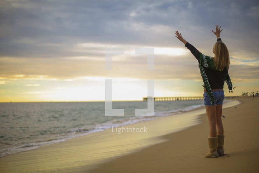 woman with raised hands on a beach