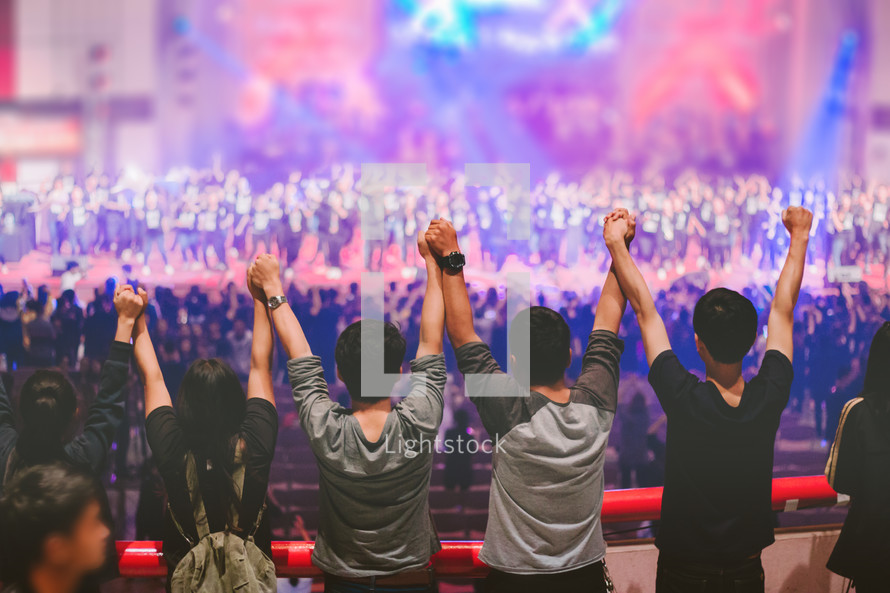 holding raised hands at a concert