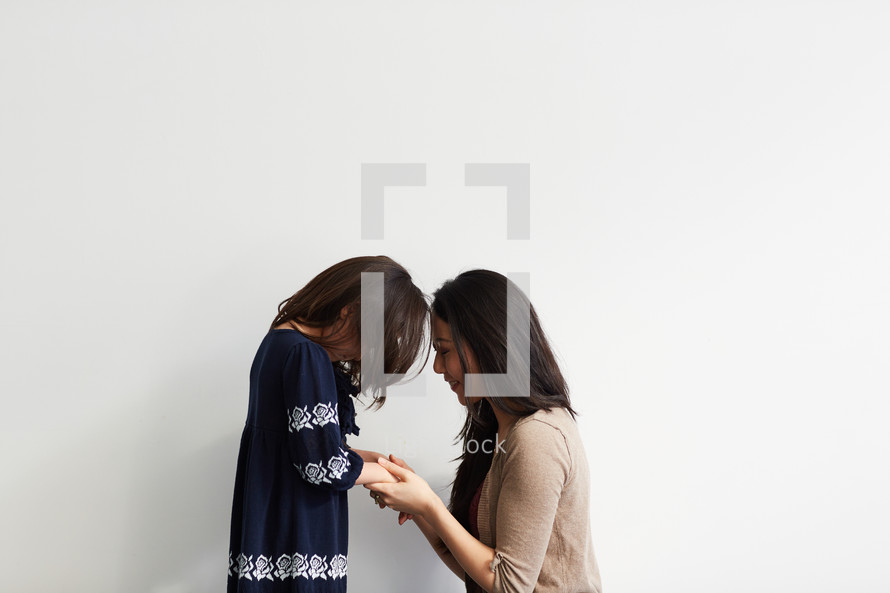 mother and daughter in studio praying together