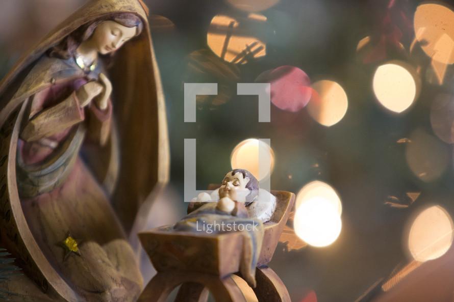 A nativity sculpture lit by Christmas tree lights.