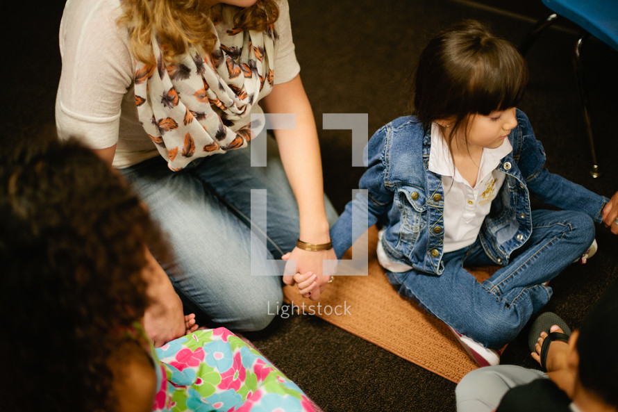 holding hands in prayer at VBS