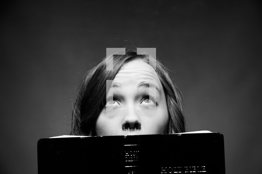 woman reading a Bible and looking up to God