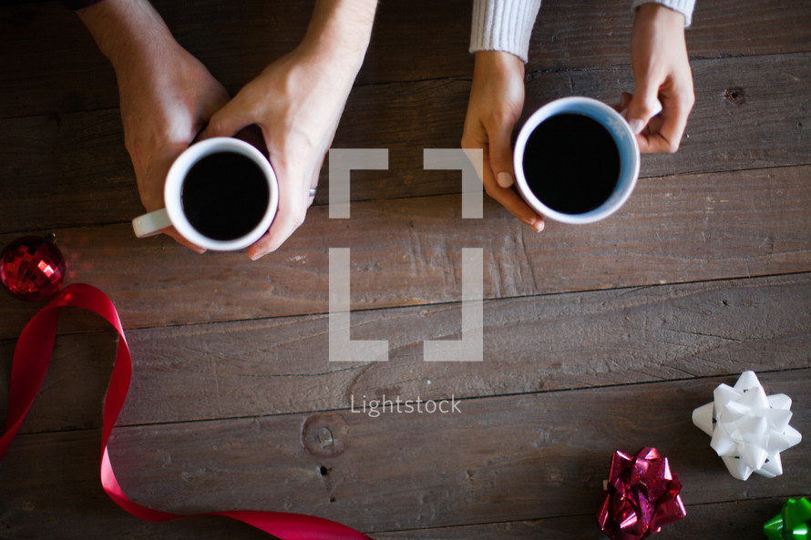 Hands holding coffee cups on a wooden table