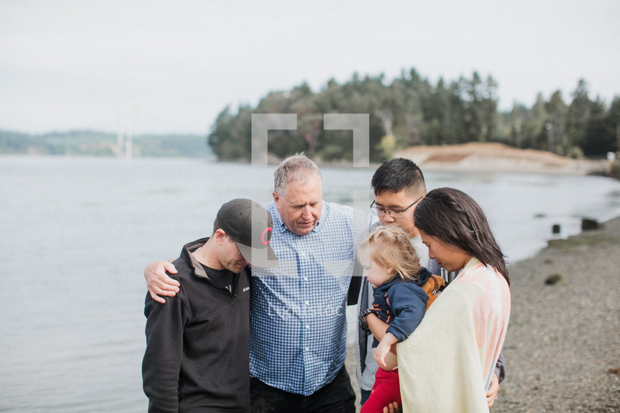 a family praying together on a lake shore