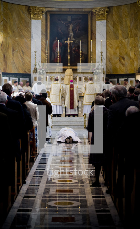 Priest prostrating during mass.