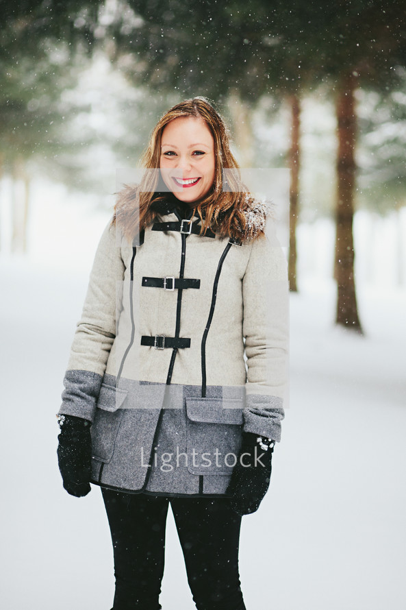 a woman in a coat standing in the snow