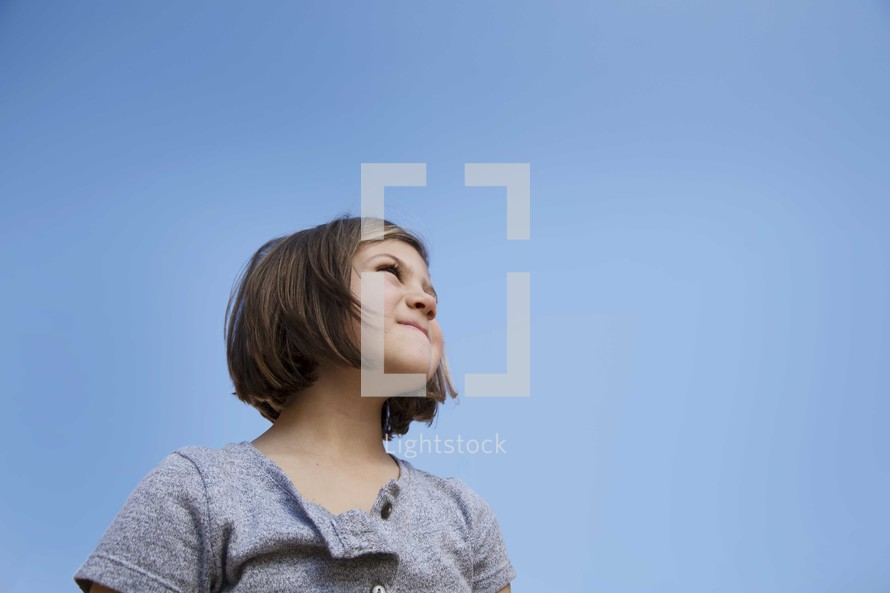 young girl standing under a blue sky