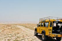 yellow jeep driving on a dirt road