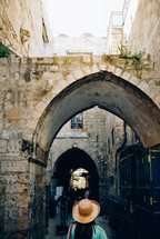 woman in a hat walking under an arched walkway