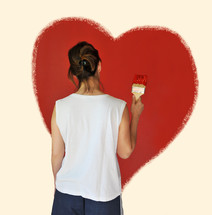 Woman painting a red heart on a wall.