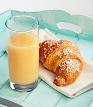 croissant and orange juice on a turquoise wood tray