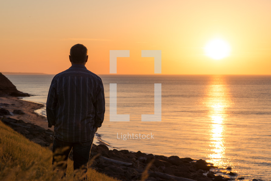 a man standing along a shore at sunset