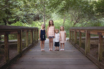 brothers and sisters standing on a wood boardwalk holding hands